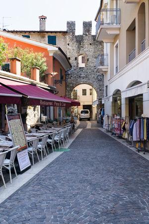 BARDOLINO, VENETO REGION, ITALY - AUGUST 7, 2017:restaurant and shops on the street in Bardolino near the San Giovanni Gate. Редакционное