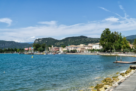 BARDOLINO, GARDA LAKE, ITALY - AUGUST 7, 2017:  Panoramic view of Bardolino with harbour and promenade. Mountains with cypresses and olive grove and vineyards in background. Bardolino is a popular holiday destination, is located in northern Italy.