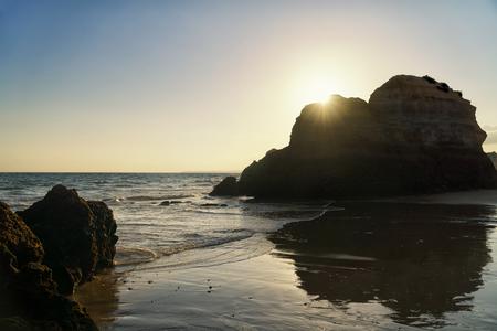 Sunset over the rock formations on a Praia da Rocha in Portimao, Algarve region, Portugal. Фото со стока