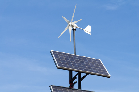 Small wind power generator and set of Solar panels agains blue sky. Concept of renevable energy.
