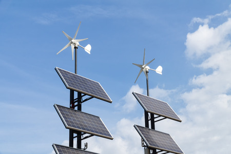 Small wind power generators and set of Solar panels agains blue sky with white clouds. Concept of renevable energy.