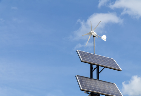 Small wind power generator and set of Solar panels agains blue sky with white clouds. Concept of renevable energy.