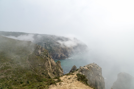 Cape Roca (Cabo da Roca) cliffs in fog. The rocks are obscured by clouds or fog. Cape Roca is most western part of Europe, Portugal. Фото со стока