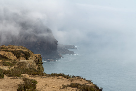 Cape Roca (Cabo da Roca) cliffs in fog. The rocks are obscured by clouds or fog. Cape Roca is most western part of Europe, Portugal. Reklamní fotografie