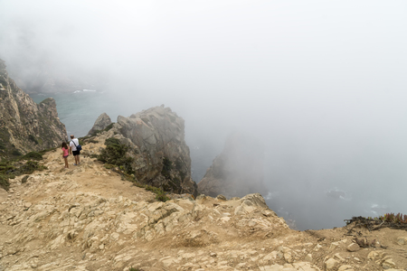 CABO DA ROCA, PORTUGAL - September 2 2018: Tourists on Cape Roca cliffs in fog. The rocks are obscured by clouds or fog. Cape Roca is most western part of Europe. Редакционное