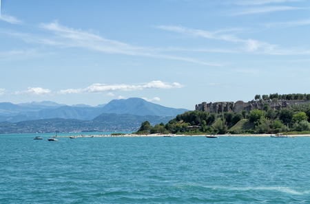 Stony Beach of Sirmione town on Garda Lake with view of Grottoes of Catullus (Grotte di Catullo), the ruins of a Roman villa built at the end of the 1st century B.C. View from Garda Lake.