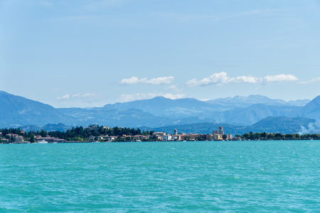 Panoramic view of Sirmione from Garda Lake with mountains in the background. Sirmione is medieval town located on the Sirmio peninsula of Lake Garda, Italy, Europe. Фото со стока