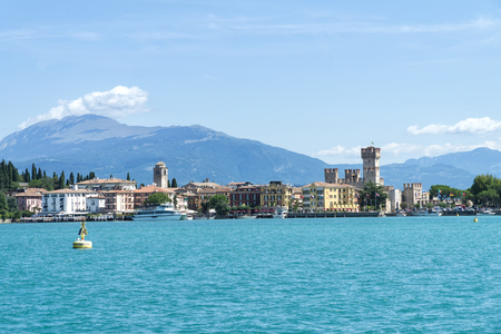 Sirmione, Italy -  August 07 2017: View of Sirmione from Garda Lake with mountains in the background. Sirmione is medieval town Sirmione, Italy -  August 07 2017: located on the Sirmio peninsula of Lake Garda, Italy, Europe. Редакционное