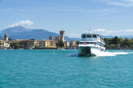 Sirmione, Italy -  August 07 2017: Tourist ship on Lake Garda. Panorama of Sirmione, Caligero Castle and mountains in the background.