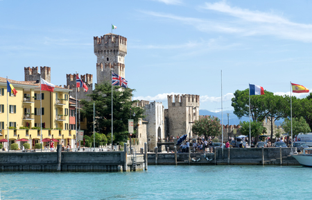 Sirmione, Italy -  August 07 2017: View of Sirmione harbor and Scaligero Castle from Garda Lake. Sirmione is medieval town located on the Sirmio peninsula of Lake Garda, Italy, Europe. Редакционное