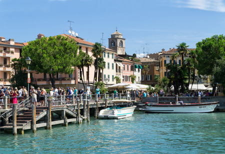 Sirmione, Italy -  August 07 2017: Tourists are waiting for a ship in the port of Sirmione on Lake Garda. Sirmione is medieval town located on the Sirmio peninsula of Lake Garda, Ital, Europe.