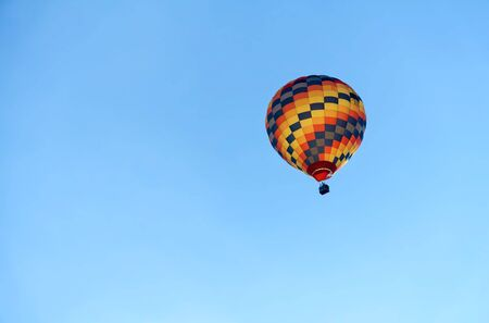 Hot air colourful baloon over blue sky. Traveling by balloon