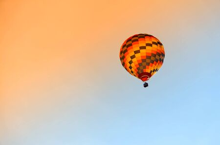 Hot air colourful baloon over blue sky.  Traveling by balloon at sunset.