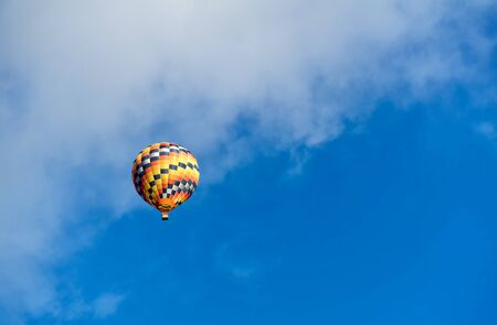 Hot air colourful baloon over blue sky with white clouds. Traveling by balloon.