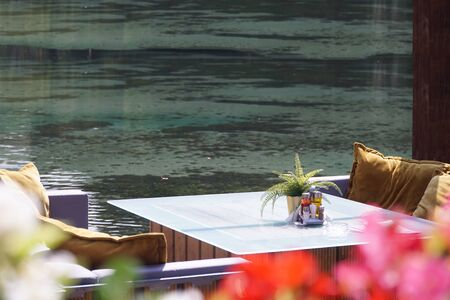 A glass table in a restaurant overlooking the lake or river with decorations, a set of spices, a pot with a plant. A sunny summer day. Nobody.