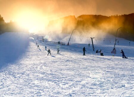 Ski resort, snowmaking on artificial slopes at sunset. Skiers and sheer snowboarders on the slope 写真素材