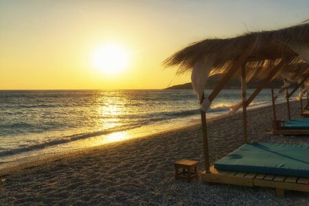 Sunset on the Livadi Beach near Himare, Albania, Europe. Beach house with sunbeds on a beach Ionian Sea coast.