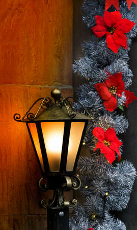 Christmas decoration with a brass lantern illuminating a stone wall and red Poinsettia flowers. Christmas concept. Christmas background. Christmas postcard. Vertical image. Reklamní fotografie
