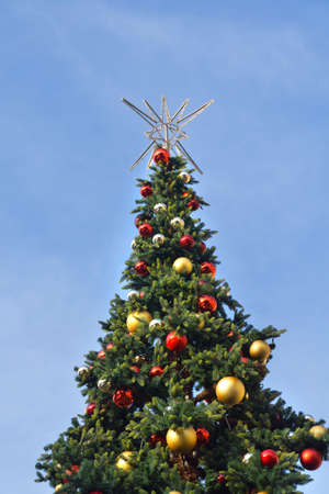 Decorated Christmas tree with red, gold and silver Christmas balls and a silver star on top against a blue sky.