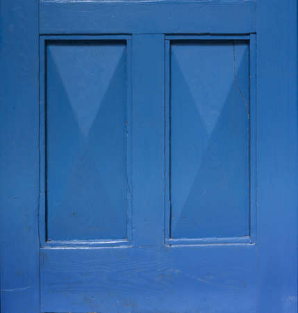 Detail of an old wooden blue painted door. Blue background. Blue rectangular frame.