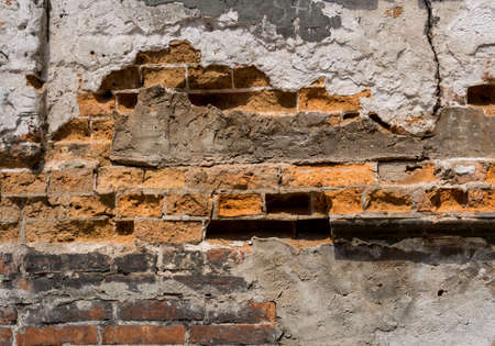 Dilapidated with potholes old brick wall of the building, made of red brick, close up. Background or texture. Reklamní fotografie