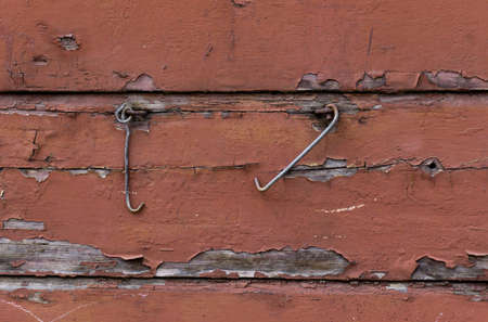 Metal shutter hooks hang on old wooden brown painted wall. Wood texture background, brown wooden planks. Reklamní fotografie