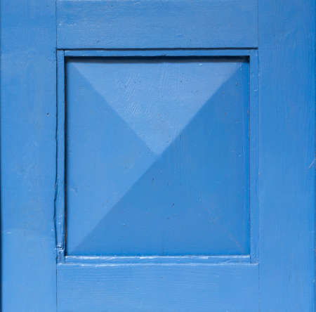 Detail of an old wooden blue painted door. Blue background. Blue square frame.