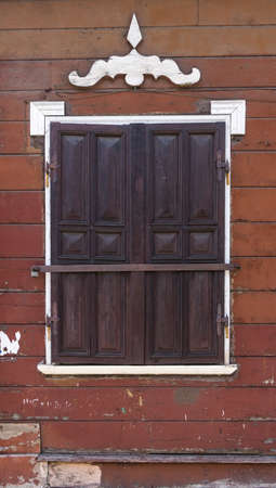 Traditional architecture detail. Brown wooden wall with window closed with wooden shutters with metal fittings and white decorative details.
