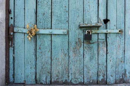 Old wooden door with blue painted planks closed with a padlock. Grunge background.