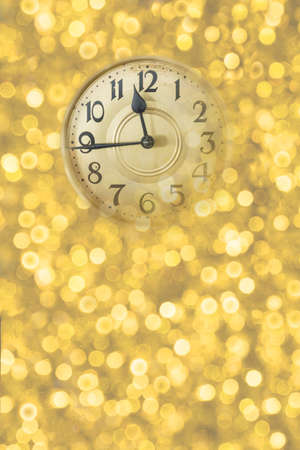 Retro style clock counting last moments before Christmass or New Year. Christmas and new years invitation golden vertical background.