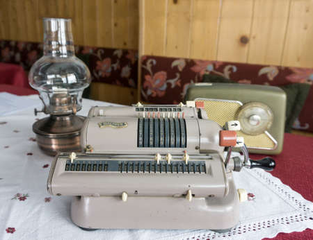 Vintage technical equipment. Walther's mechanical calculating machine with vintage radio receiver and kerosene lamp in background. Redakční