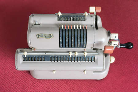 Vintage technical equipment, Walther's mechanical calculating machine with vintage radio receiver and kerosene lamp in background.