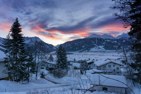 Sunset over the mountains. Winter mountain landscape. Dark blue sky with dramatic coluds. Ehrwald, Austria, Europe. Reklamní fotografie