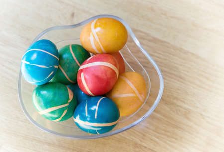 Pile of colorful painted homemade easter eggs with modern pattern in glass bowl on wooden table. Easter decoration, easter background.