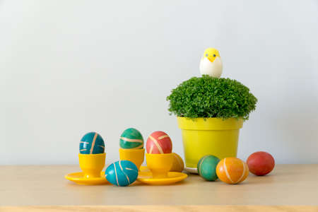 Easter decoration with colorful painted homemade easter eggs with modern pattern on yellow coasters and watercress in pot on wooden table. Easter background with copy space. Reklamní fotografie