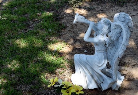 Cemetery stone sculpture angel playing horn with space for copy background.
