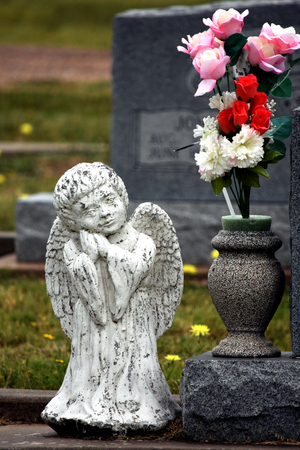 Small child cemetery headstone angel white stone with flowers.
