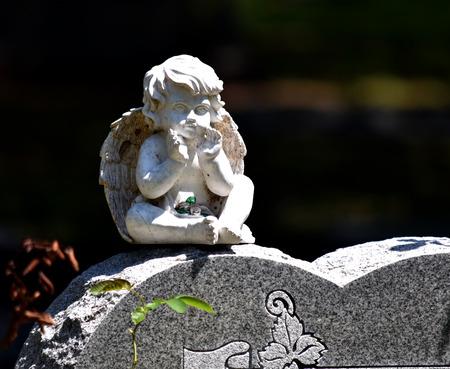 Sitting child angel headstone cemetery sculpture white stone.