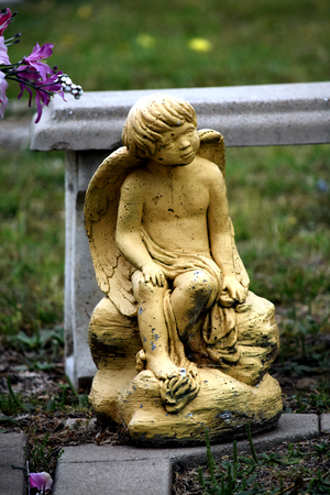 Sitting child angel headstone sculpture gold color stone.