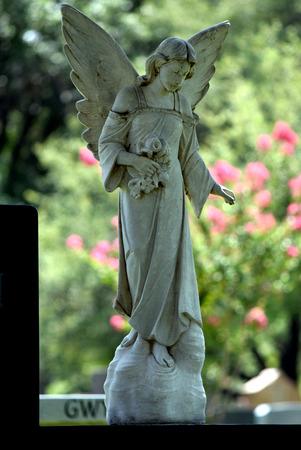 Female angel white stone cemetery headstone, guardian of tomb. Stock Photo