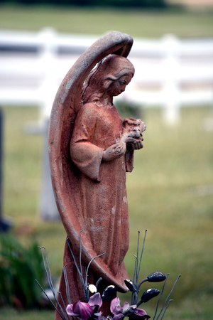 side view cemetery angel with full wings and terracotta colored.