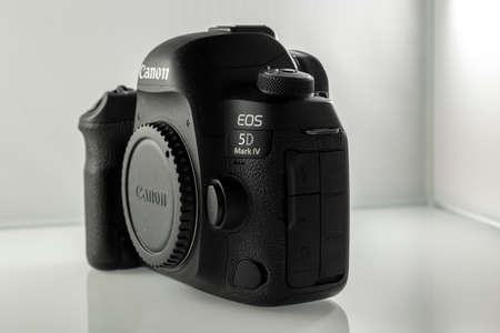 Frankfurt, Germany - 21st March 2021: A german photographer taking pictures of the Canon EOS 5D Mark IV camera body from all sides incl. Buttons and connections in order to sell it on eBay. Publikacyjne