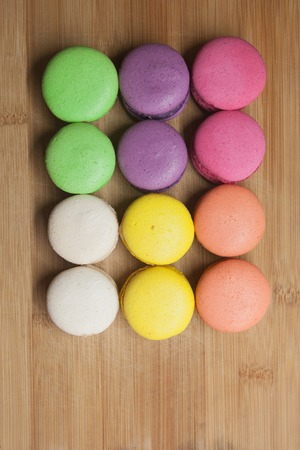 indulgence: macaroons on the wooden coffee desk in vintage color tone Stock Photo