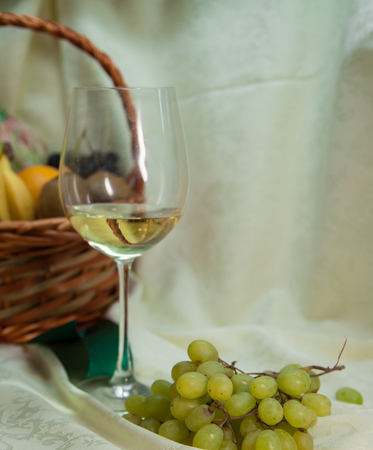 aligote: wine and fresh fruits in a basket on a vintage background