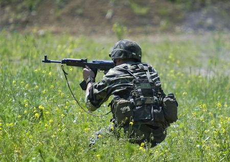 Soldier in action firing his automatic rifle kalashnikov