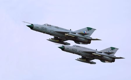 Pair of MiG-21 Fishbed fighters flying in tight formation               Stock Photo