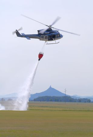 Bell-412 police helicopter dropping water to put out fire