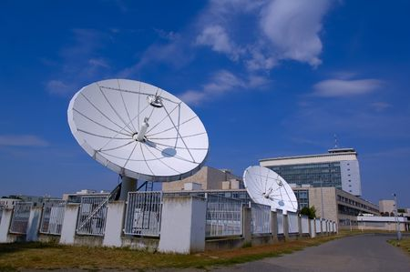 white satellite dishes with blue summer sky in background