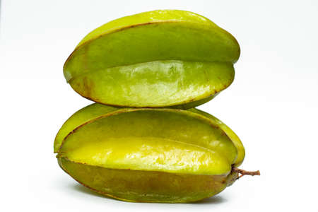 Two green carambola fruit on a white bg