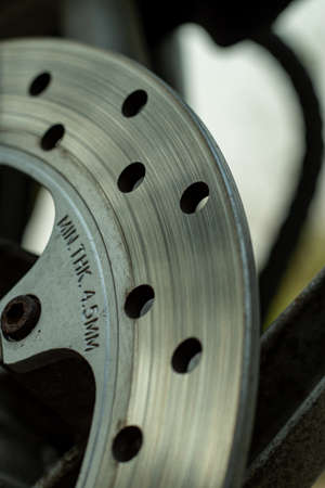 Motorcycle brakes that make heavy metal or iron or steel plates with round holes in them
